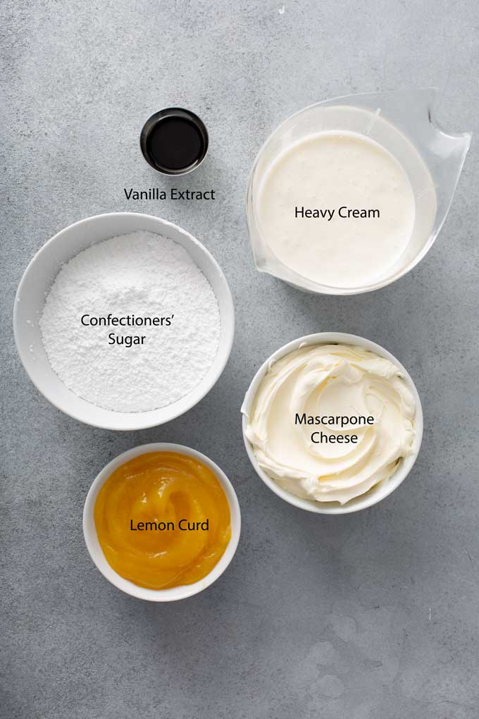 Ingredients to make whipped mascarpone frosting on a gray surface