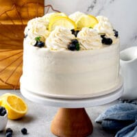 a whole 3 layer cake covered with mascarpone frosting and garnished with blueberries and lemon slices