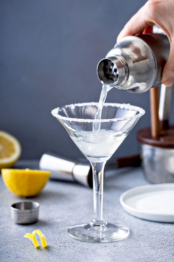 Cocktail shaker pouring lemon martini   in a glass