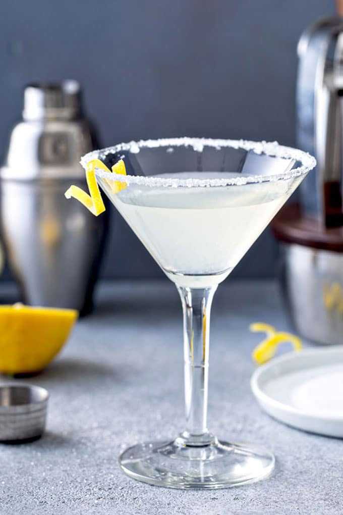 A martini glass with lemon drop martini cocktail and a lemon twist on a gray counter
