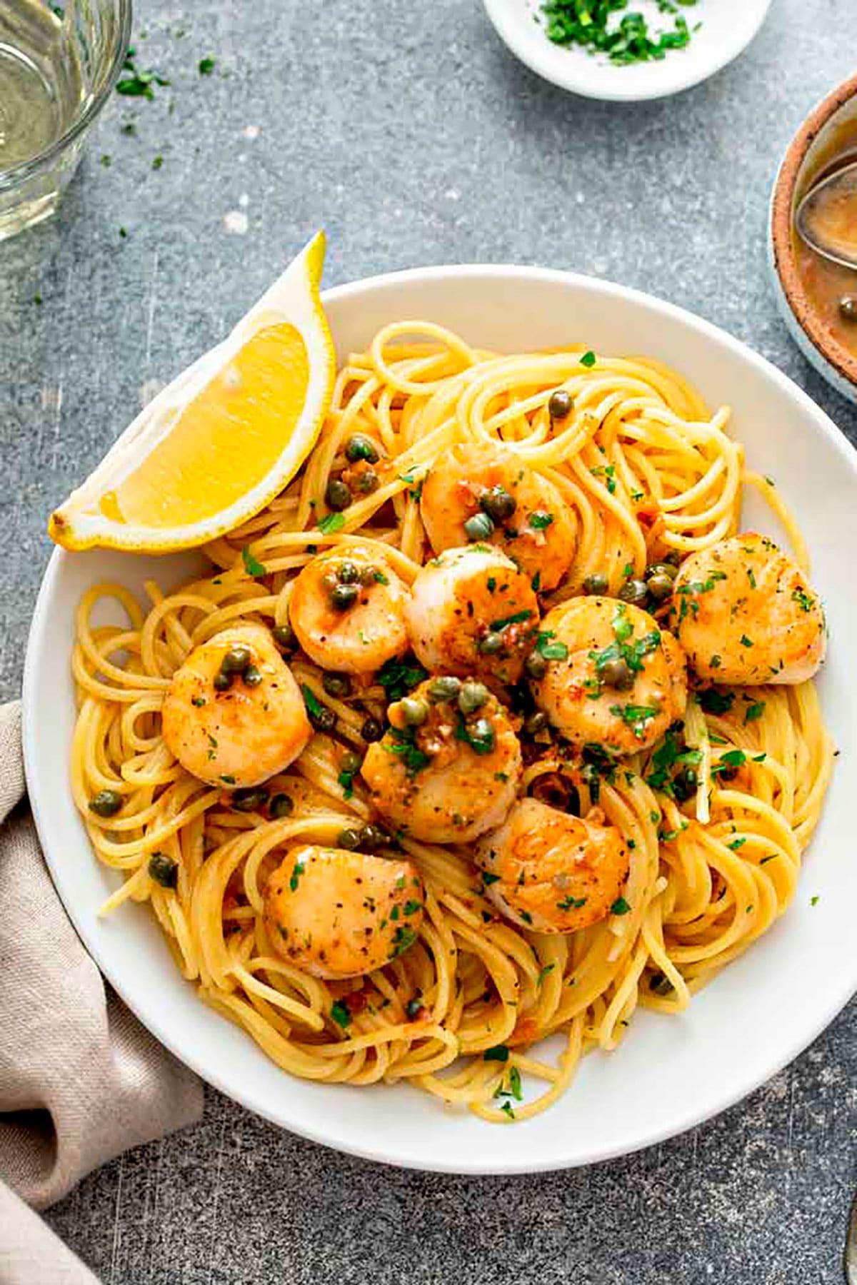 Seared scallops over pasta in a white plate.