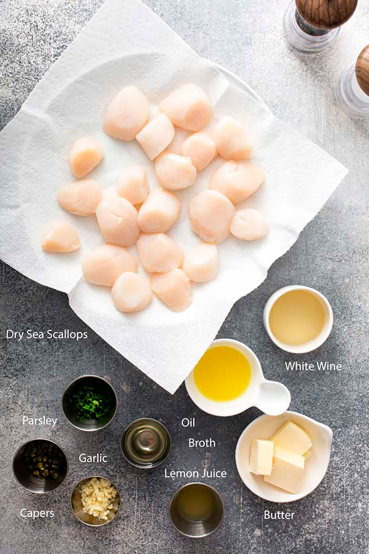 Ingredients to make seared scallops with lemon garlic butter sauce on a gray surface