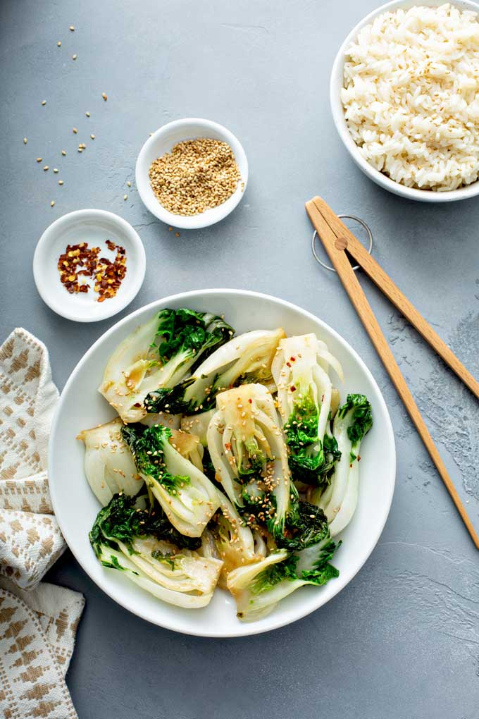A bowl filled with stir fried bok choy on a gray surface