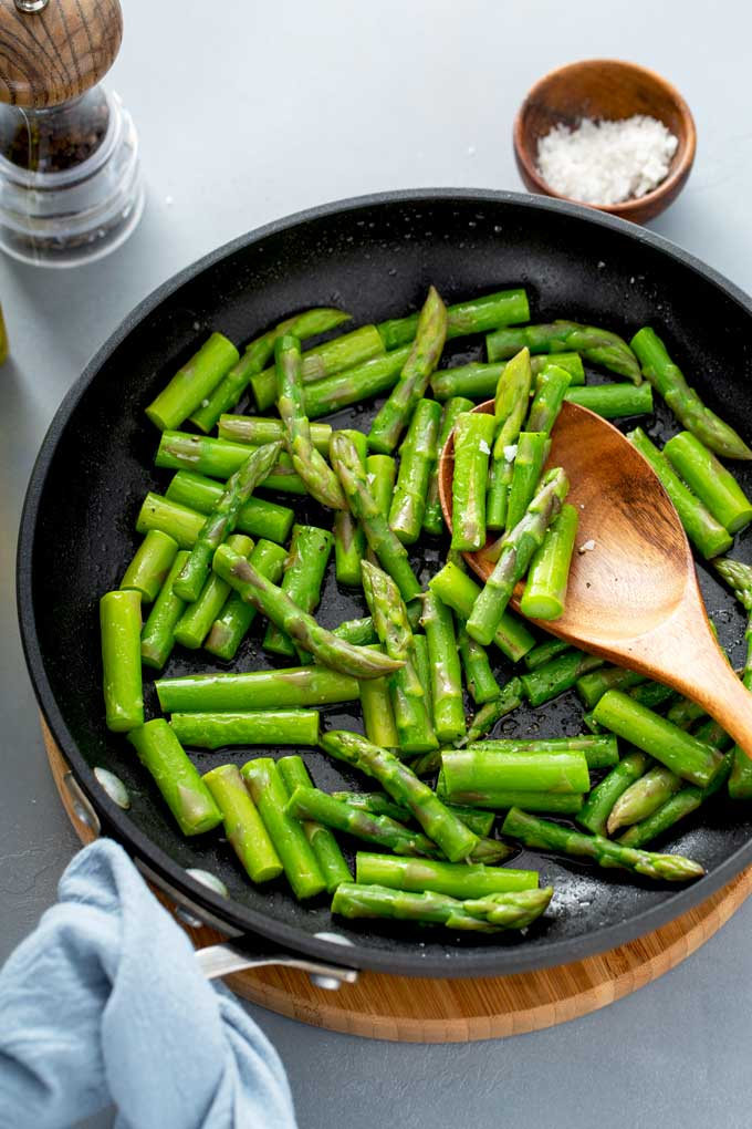 Asparagus cut into bite size pieces in a skillet.