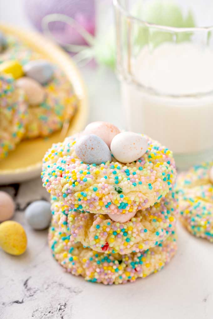 Three Easter cookies stacked together on a white marbled surface.