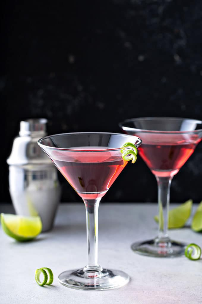 A couple of cosmopolitan cocktails on a white surface next to a cocktail shaker