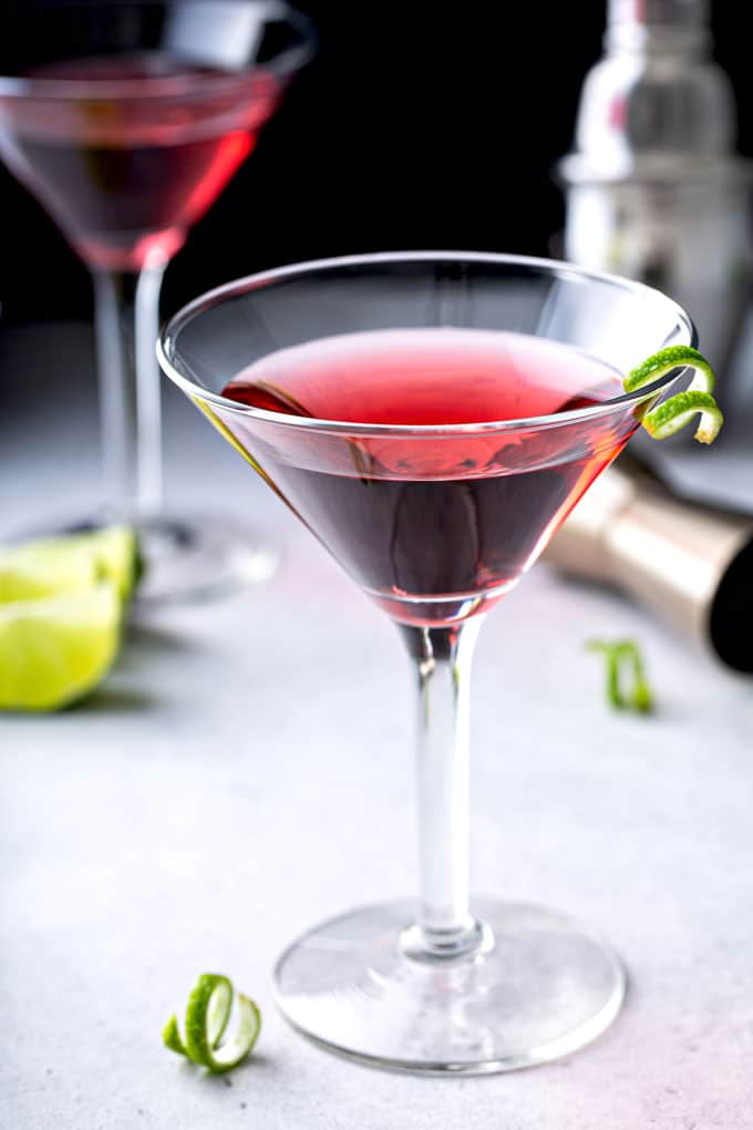 A martini glass filled with cosmopolitan cocktail martini on a light surface