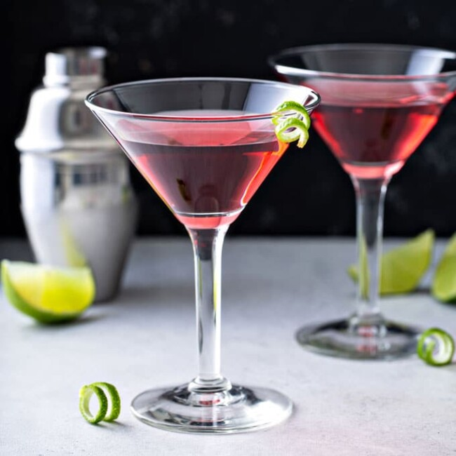 Two Cosmopolitan Martinis on a white surface