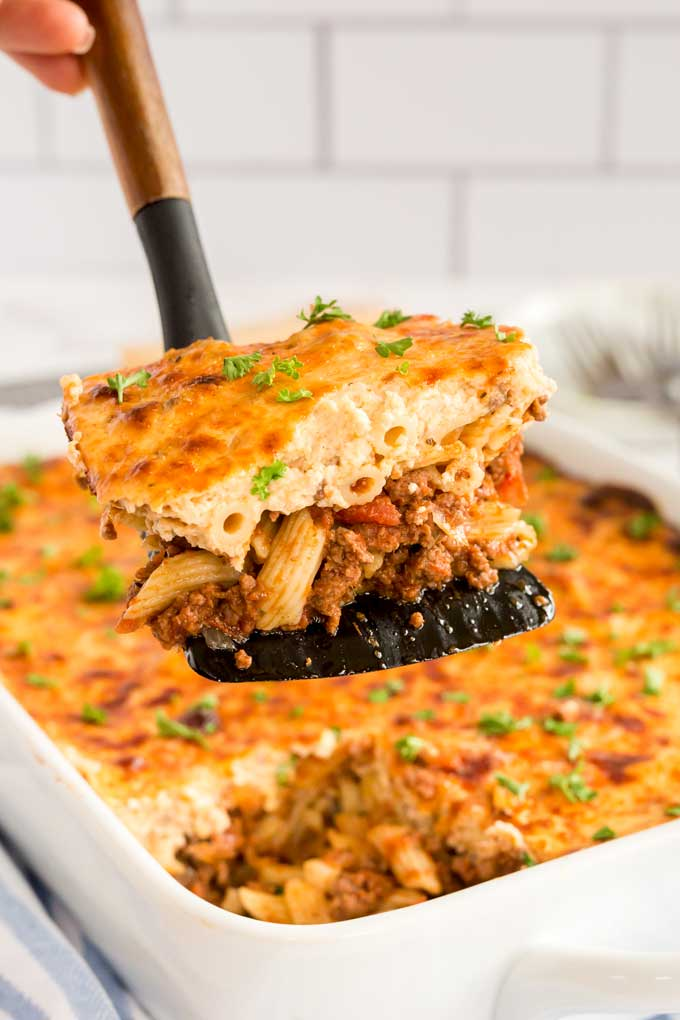 A slice of pastitsio getting served from a baking dish
