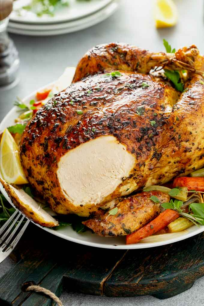 A whole roast chicken with a piece of breast sliced off on a white plate.