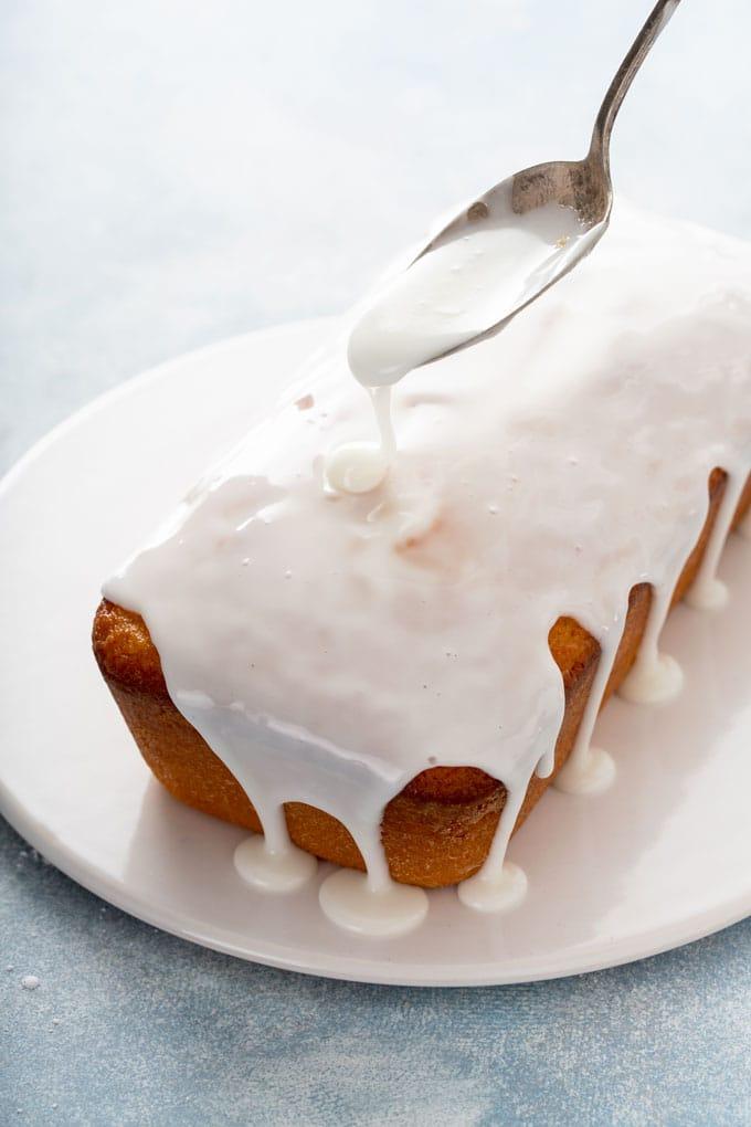 Lemon glaze getting poured over loaf cake.