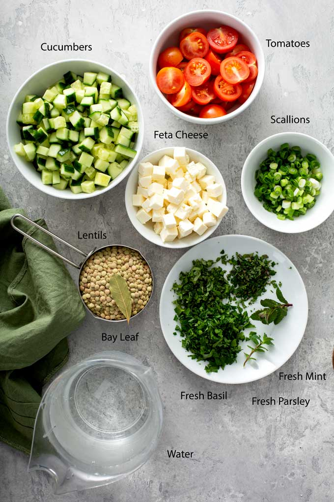 Ingredients to make lentils salad on a gray surface