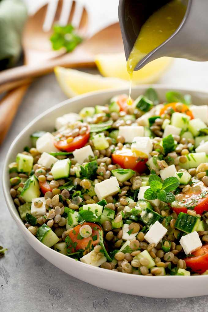 Lemon salad dressing getting poured over lentils salad