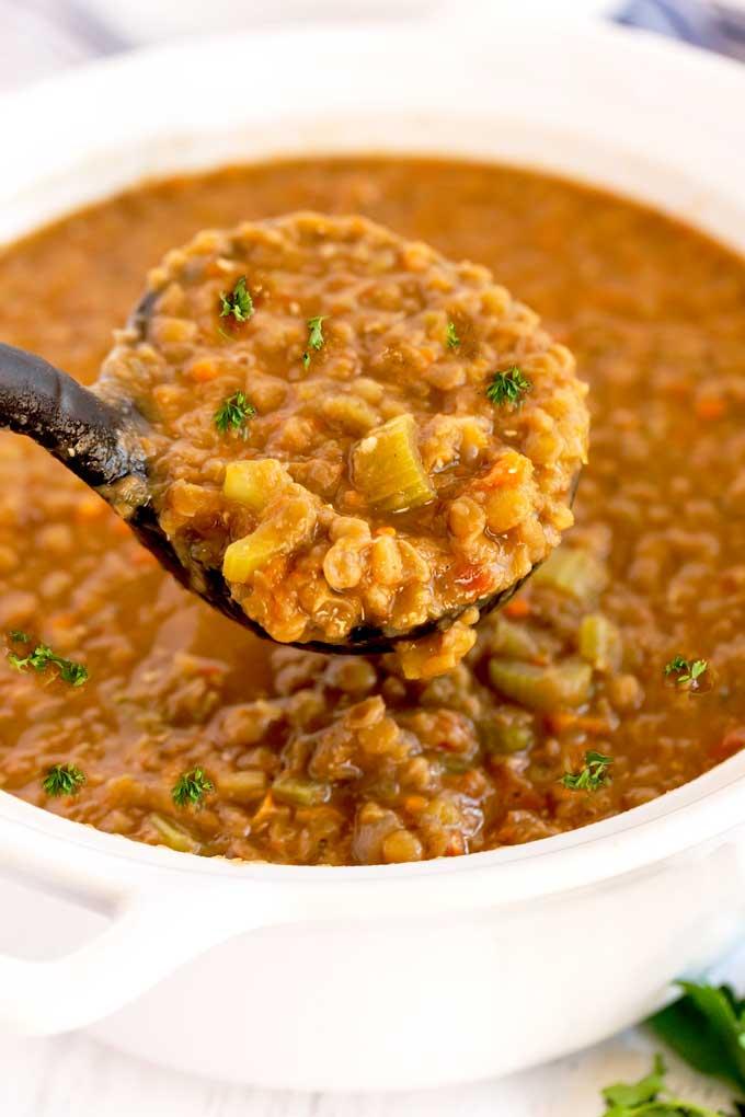 Soup ladle serving soup from a white ceramic soup pot