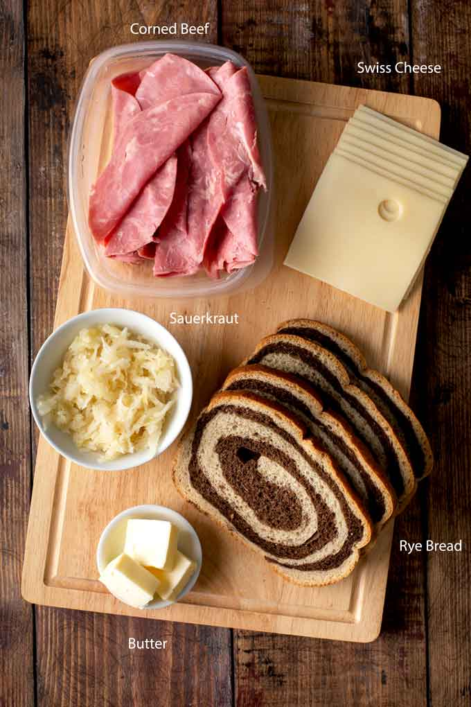 Ingredients to make a Reuben on a wooden board.