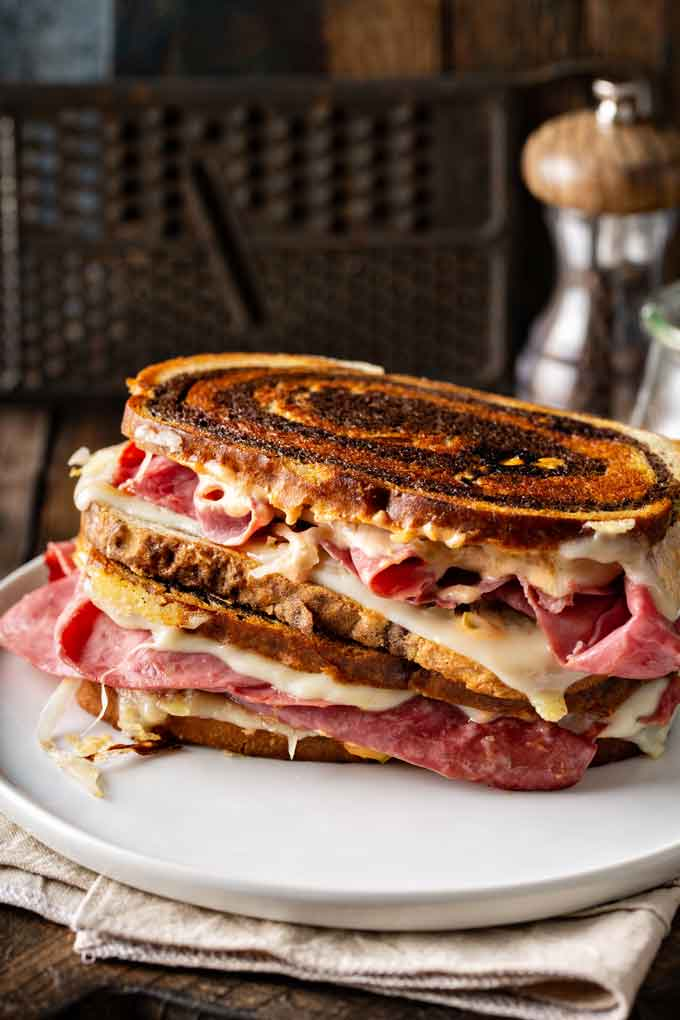 Two grilled Reuben sandwiches, one on top of the other on a white plate