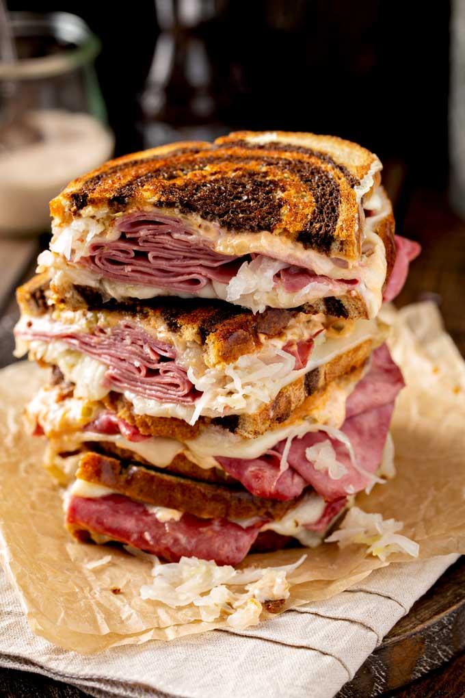 Corned beef sandwiches cut in half and stack on top of parchment paper