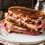 Two Reuben sandwiches stacked on a white plate
