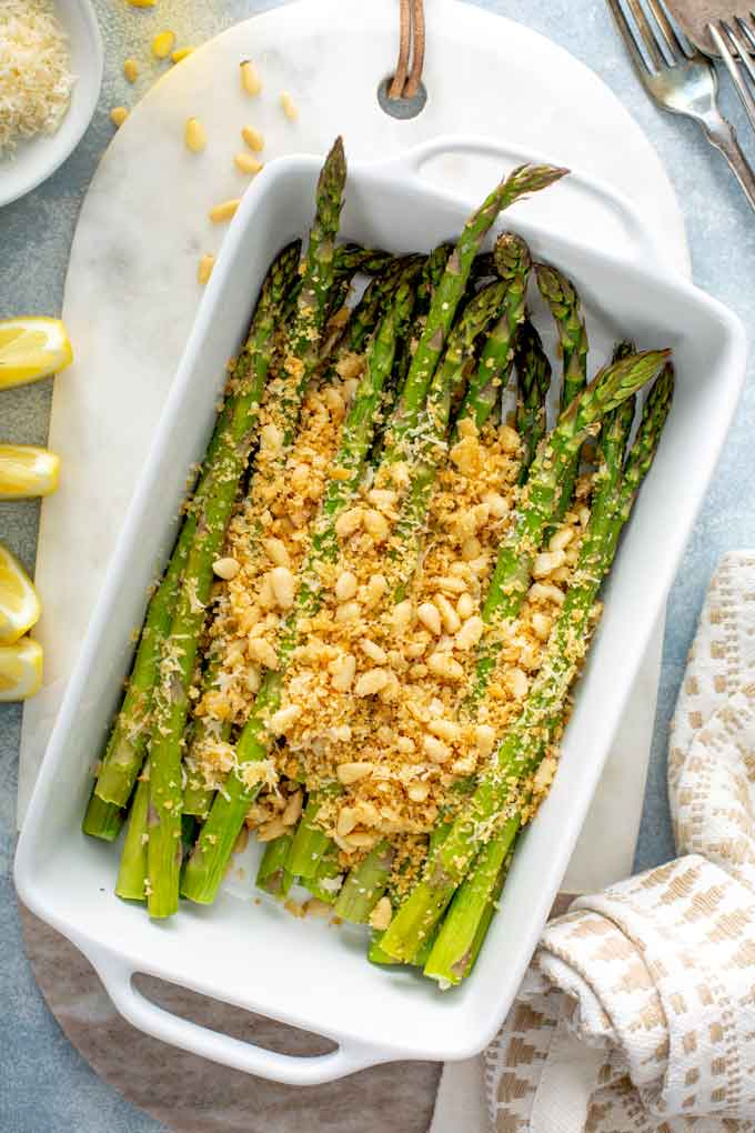 Oven roasted asparagus with Parmesan topping in a small white dish