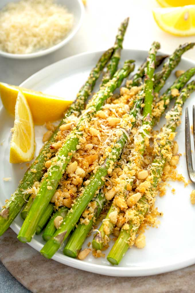 Roasted asparagus topped with a crispy buttery cheesy topping and pine nuts.