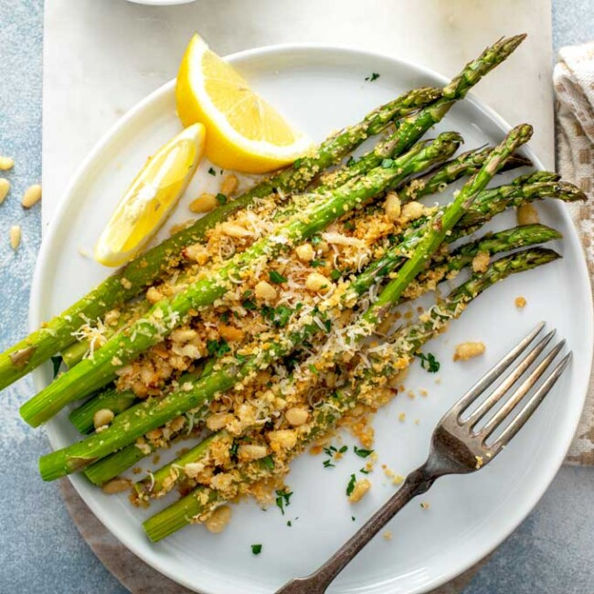 Roasted Asparagus with a crispy Parmesan topping on a white plate.