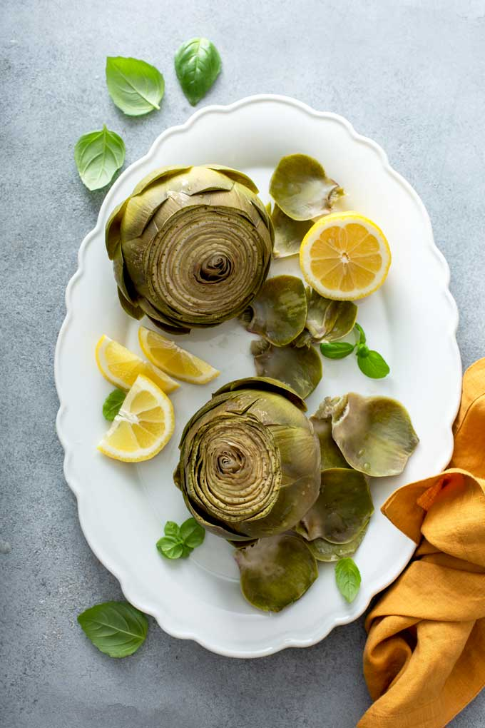 Artichokes on a white platter with lemon slices