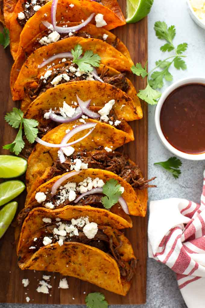 Several birria tacos on a wooden board