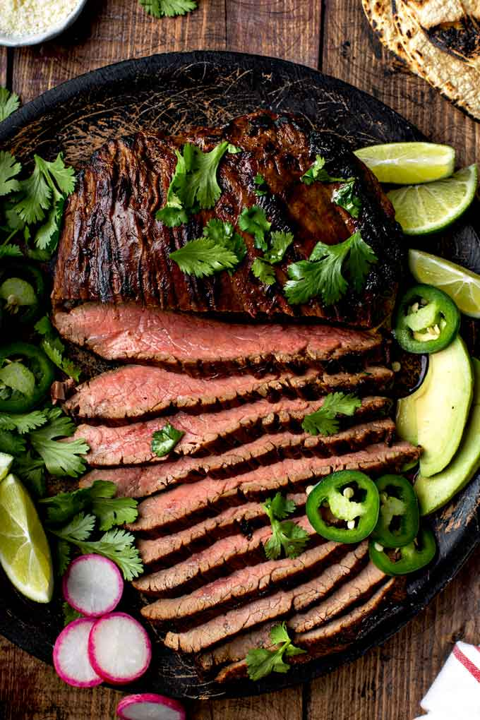 Top view of sliced flanked steak grilled and served with Mexican fixings.