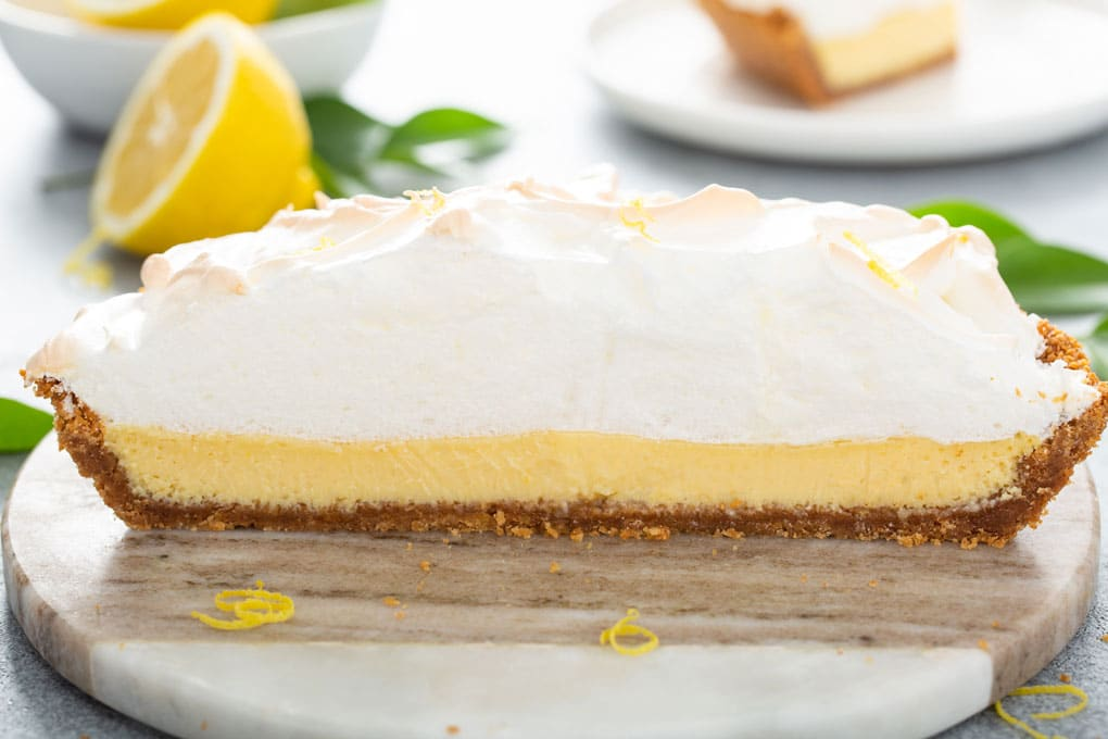 Side view of a lemon pie cut in half showing the creamy center and the fluffy meringue