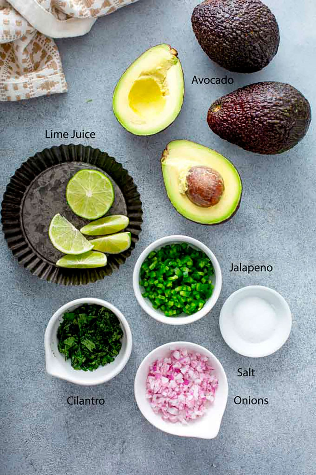 Ingredients  to make guacamole on a gray surface