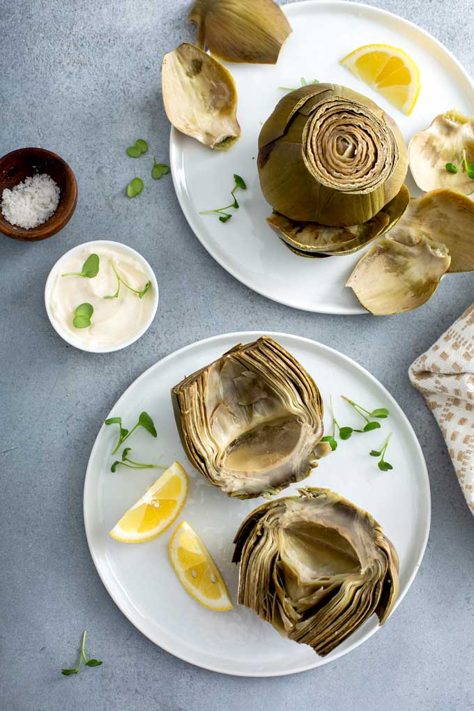 Artichokes on white plates served with lemon slices and dipping sauce