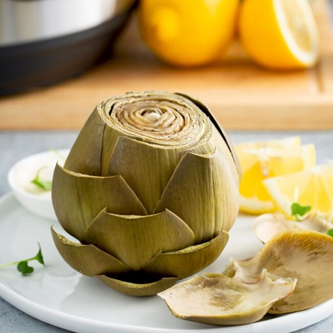 Cooked whole artichoke on a white plate