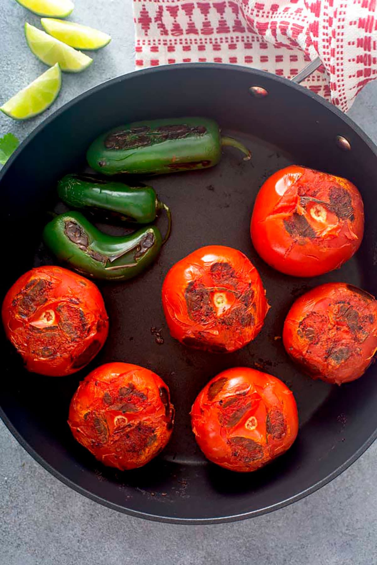 Tomatoes and jalapeños getting charred in a skillet