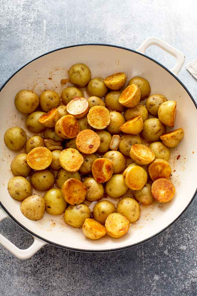Golden baby potatoes cut in half cooking in a skillet.