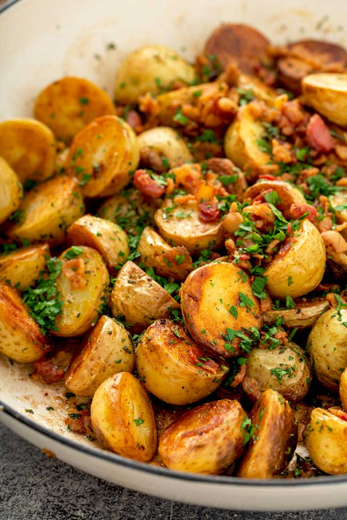 Crispy golden potatoes with bacon in a skillet.