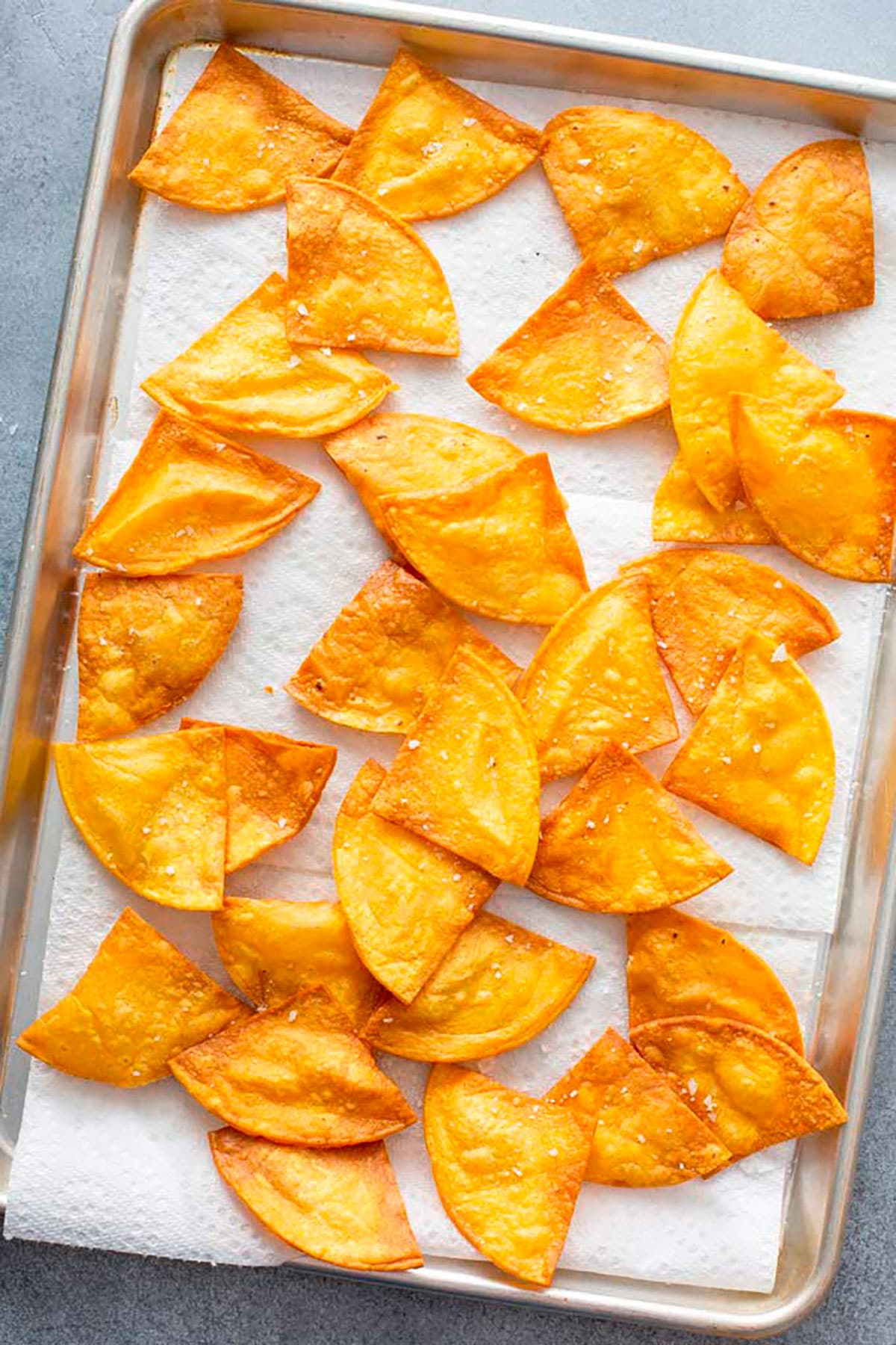 Paper towel lined sheet pan with freshly cooked tortilla chips