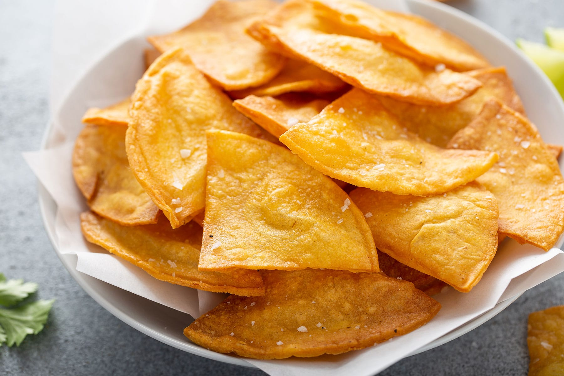 Freshly made tortilla chips in a bowl.