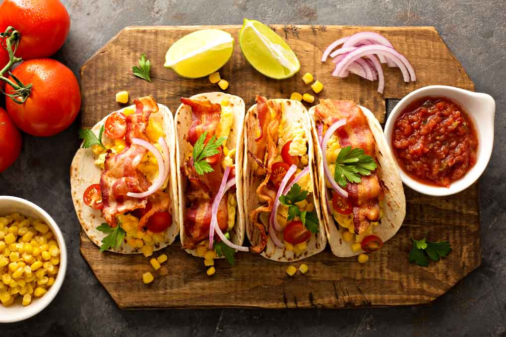 Top view of four breakfast tacos with eggs and bacon
