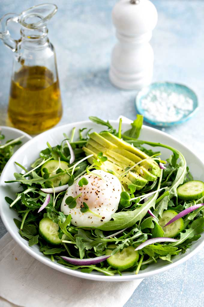 poached egg on a salad with cucumbers  and avocado