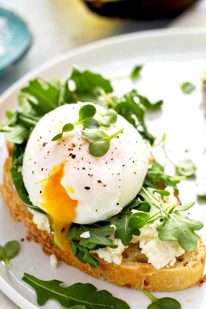 poached egg with a runny yolk on a piece of toast with arugula