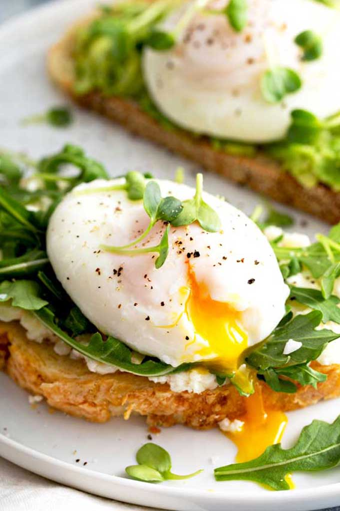 Poached egg with runny yolk on top of a toast with crumbly cheese and arugula