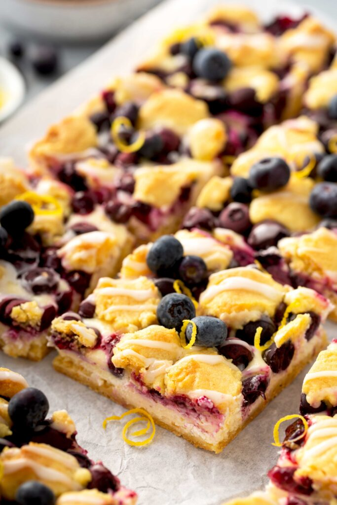 Cut up cheesecake crumb bars with blueberries on parchment paper.
