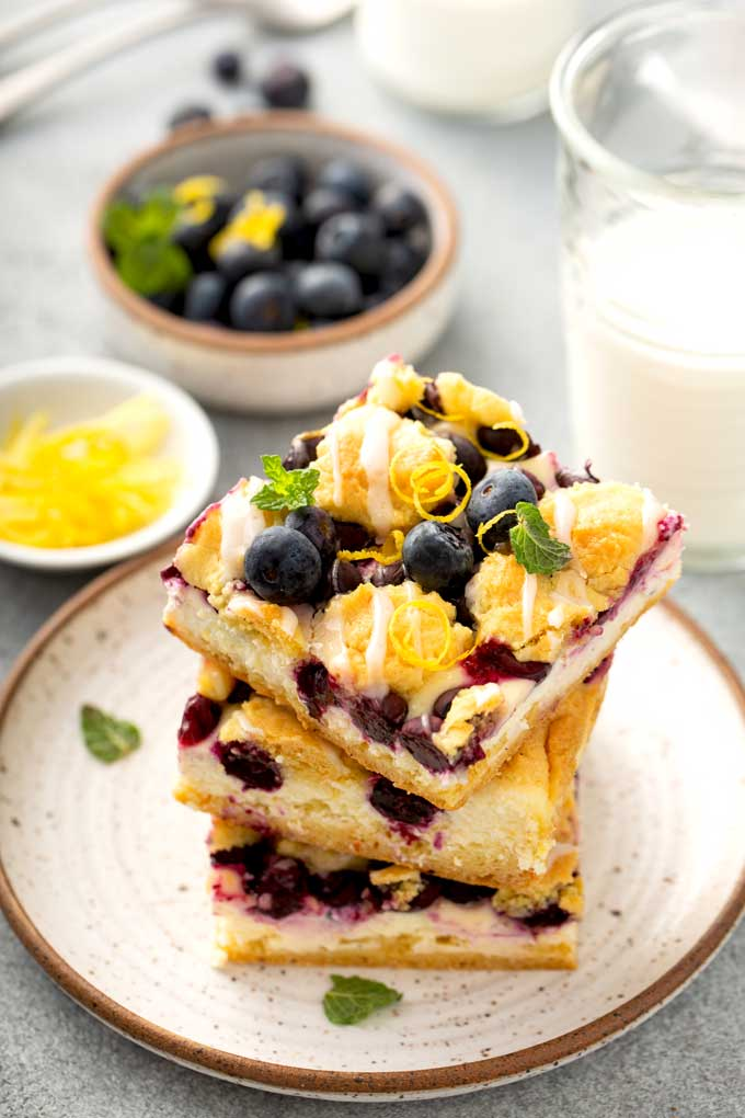 A stack of fruity crumb bars on an ivory plate