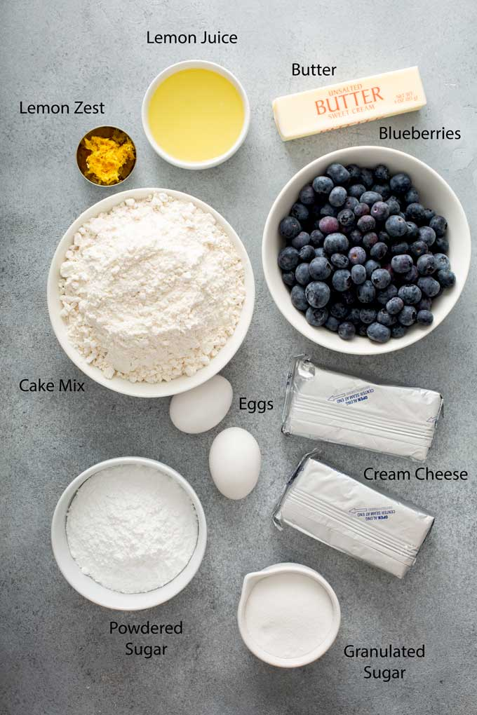 Ingredients to make lemon blueberry crumble bars on a gray surface