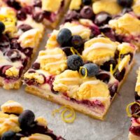 Lemon Blueberry crumb bars cut into squares on a piece of parchment paper