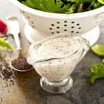 small glass pitcher with lemon poppy seed dressing