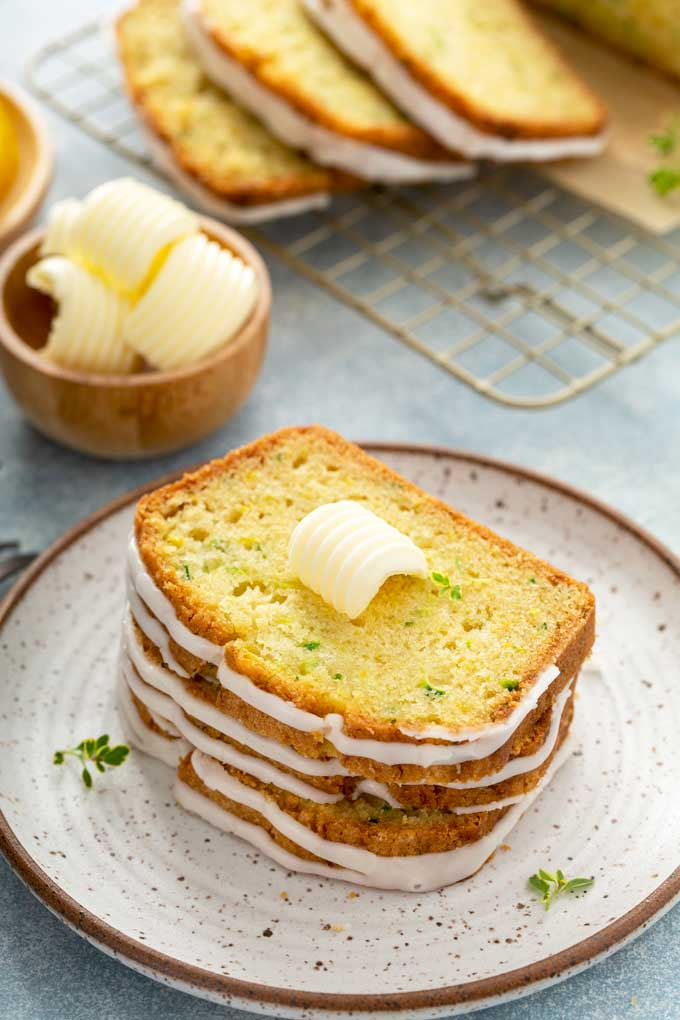 Slices of bread topped with a pad of sweet butter on a plate