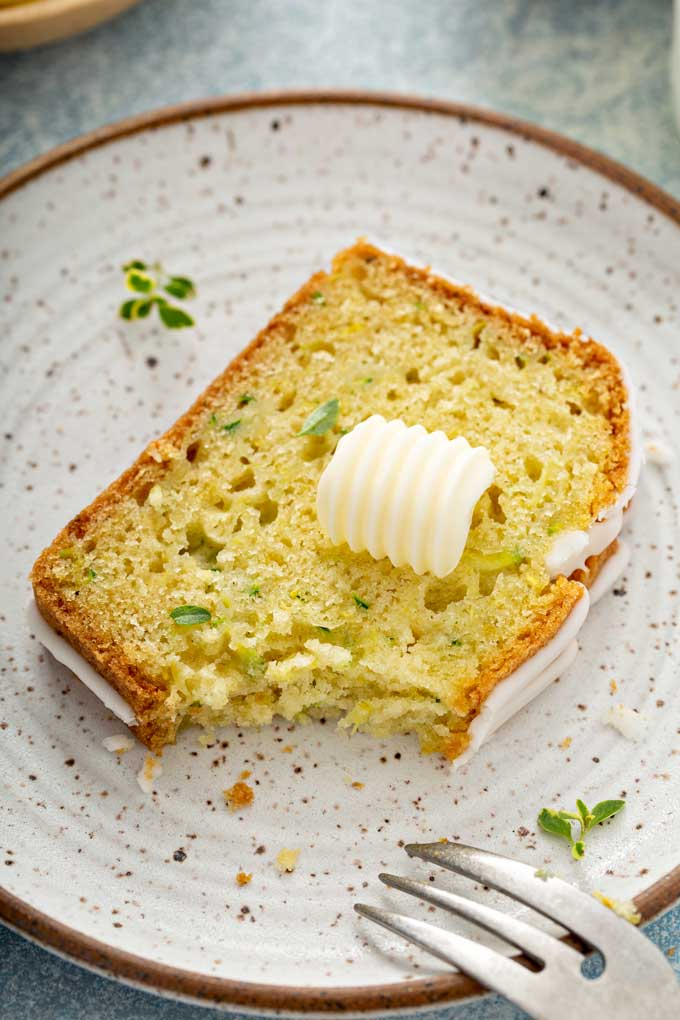 A sliced of zucchini lemon bread topped with a pad of butter on a plate