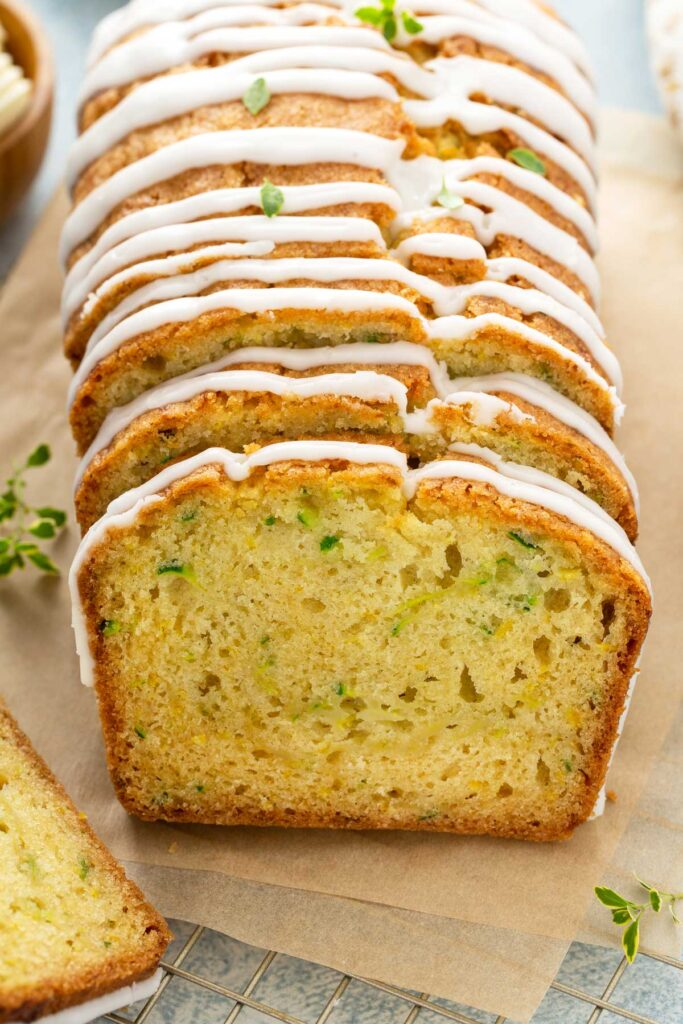 Sliced zucchini bread with lemon glaze drizzle on parchment paper.