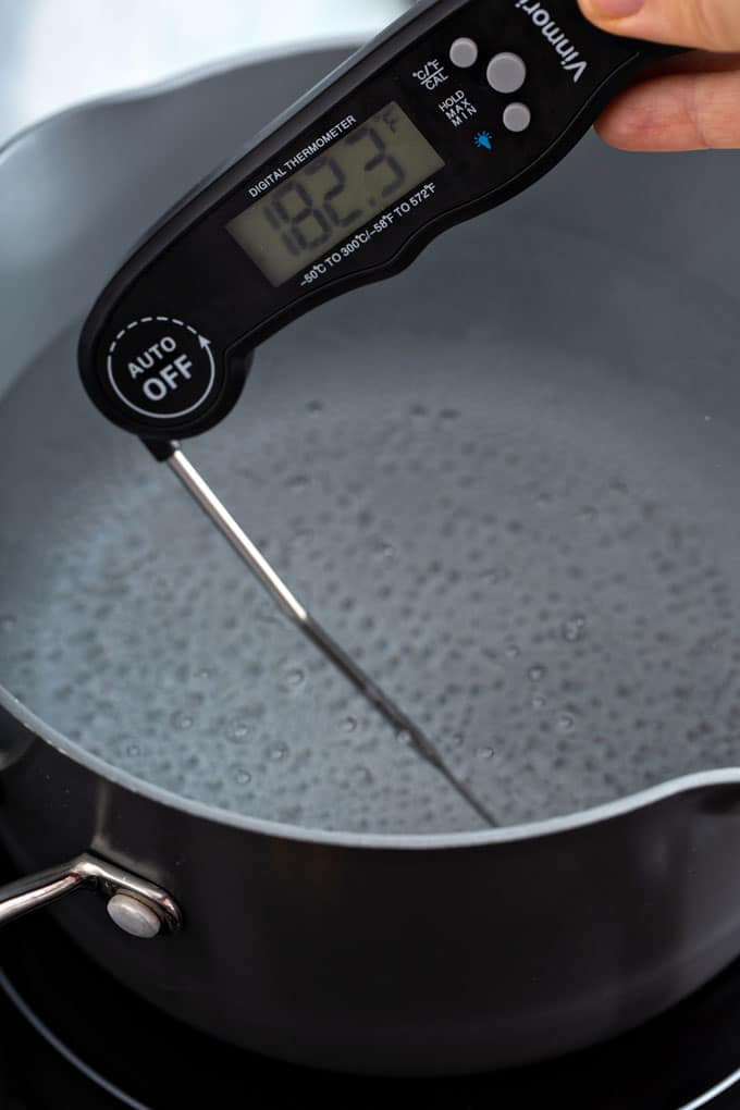 Thermometer checking the temperature of simmering water
